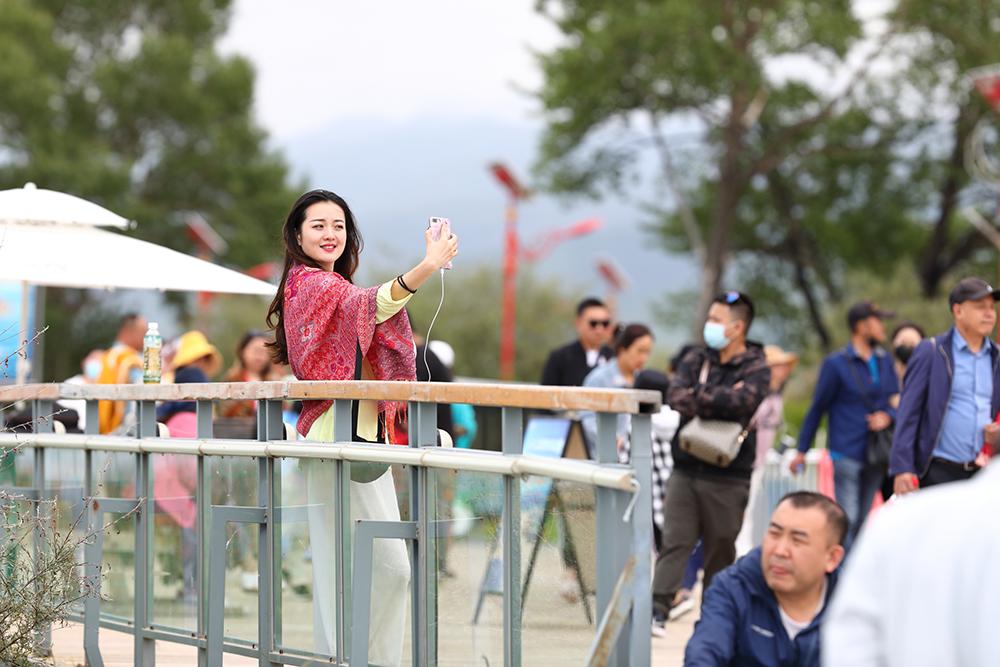 7月27日,青海湖,一位游客在拍照。刘欢摄